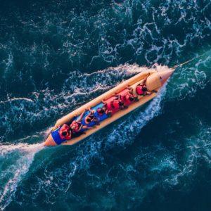 People having fun on a banana boat in Barcelona